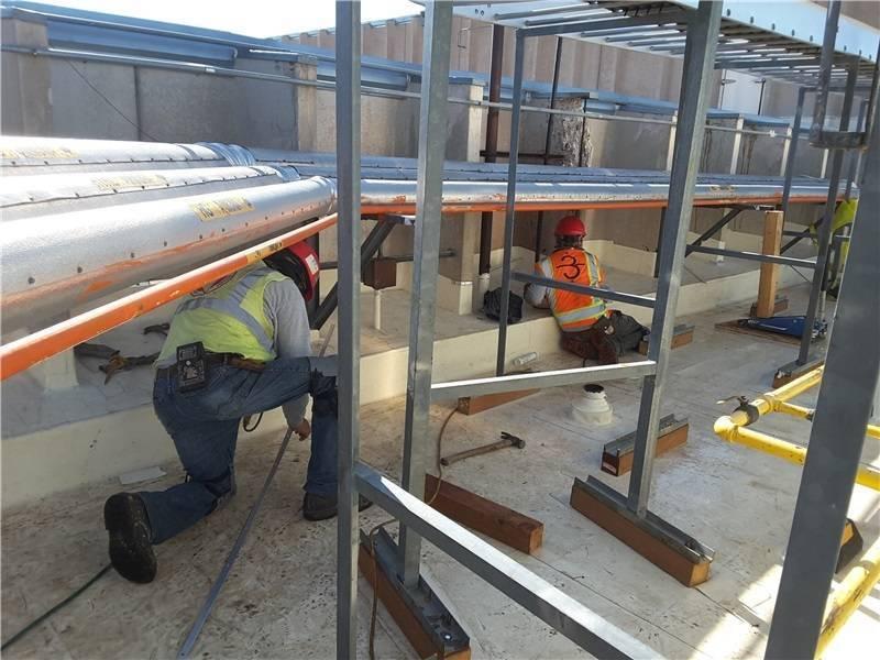Rooftop contractors work safely around utility lines.